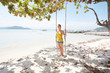 Young woman standing on swing at beach