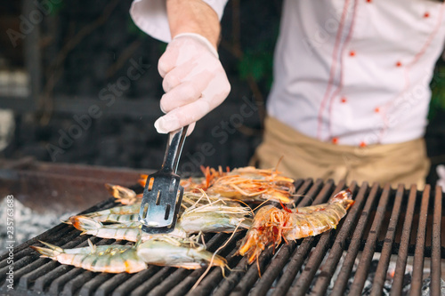 The chef cooks lobster on the grill.