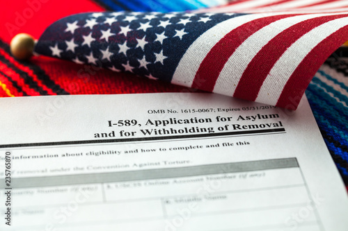 Photo Application for asylum to USA concept with application form and USA flag on mexi
