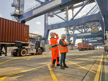 Dock Workers Using Tablet PC A...
