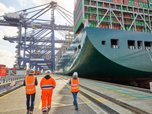 Dock Workers By Cargo Ship At Port Of Felixstowe, England
