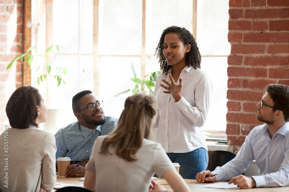 Fototapeta African American woman standing and talking about new project, opinion, business strategy at briefing, company meeting, multiracial colleagues group looking attentively at speaking businesswoman