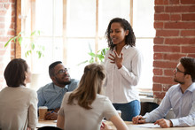 African American Woman Standing And Talking About New Project, Opinion, Business Strategy At Briefing, Company Meeting, Multiracial Colleagues Group Looking Attentively At Speaking Businesswoman