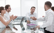 handshake business partners over the Desk