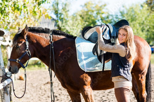 Poster Equitation Girl equestrian rider equips horse. Horse theme