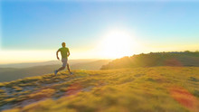 LENS FLARE: Athletic Young Man Sprints Down A Grassy Hill On A Sunny Morning
