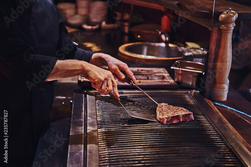 Master chef wearing uniform cooking delicious beef steak on a kitchen in a restaurant. - 235787827