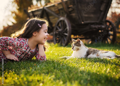 Tuinposter Artist KB Cute little girl smiling to a cat