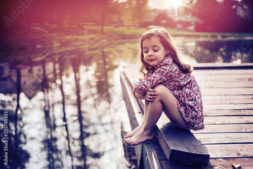 Cute little girl relaxing by the lake Wallpaper Mural