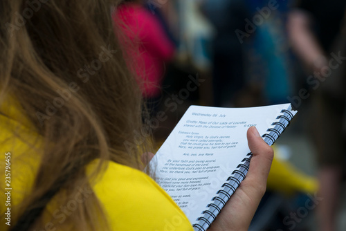 Photo  LOURDES, FRANCE - JULY 6, 2016: A young girl reads a book of religious songs, while celebrating Mass, near the Shrine of the Virgin