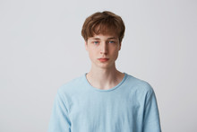 Headshot Of A Blue-eyed Guy Without Emotions. Emotionless Teenager In A Blue T-shirt Looking To The Camera, Isolated Over White Background
