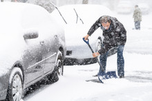 Young Man, Male In Winter Coat Cleaning, Shoveling Driveway, Street From Covered Falling, Snow In Heavy Snowing Snowstorm With Shovel, Residential Houses, Cars Parked On Road