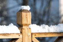 Closeup Of Wooden Deck Fence Railing, Pole, Post Covered, In Piled, Pile Of Snow After Heavy Snowing Snowstorm, Storm At House, Home, Residential Neighborhood In Background, Trees, Sunlight