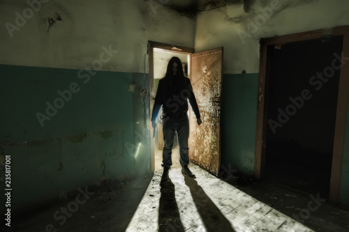 Photo  Serial killer maniac with knife in dark abandoned building