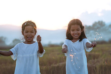 Two Cute Asian Child Girl Are Playing With Fire Sparklers On The Festival In The Rice Field At Sunset Time
