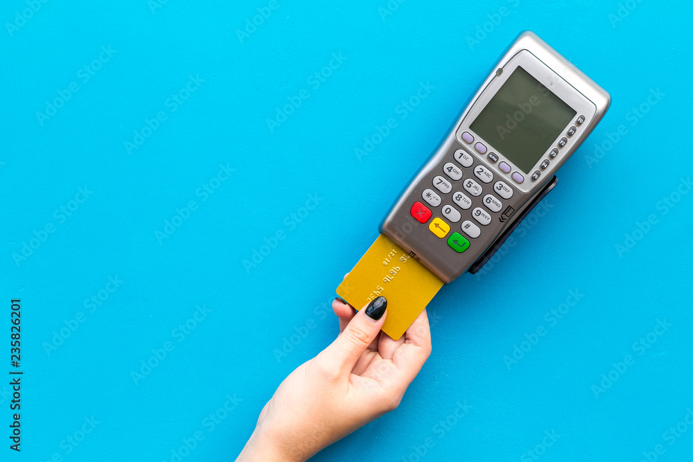 Fototapeta Pay by payment terminal. Woman's hand inserts credit card to terminal on blue background top view copy space