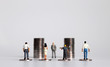 canvas print picture - Miniature people with piles of coins. The concept of workers demanding a minimum wage increase.