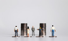 Miniature People With Piles Of Coins. The Concept Of Workers Demanding A Minimum Wage Increase.