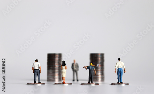 Foto Miniature people with piles of coins