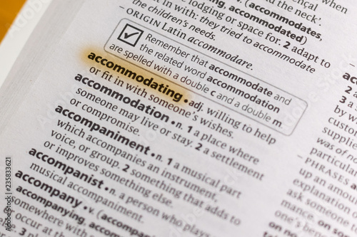 Photo The word or phrase Accommodating in a dictionary.