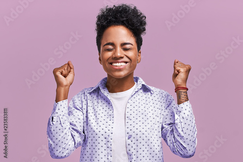 Fotomural  Horizontal shot of happy mixed race female clench fists with happiness, being sa