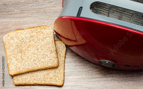 Modern toaster with toasted sliced  bread on wooden background. Kitchen equipment.Top view