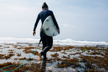 Woman Surfer With Surfboard Walking On Seaside Mossy Reefs