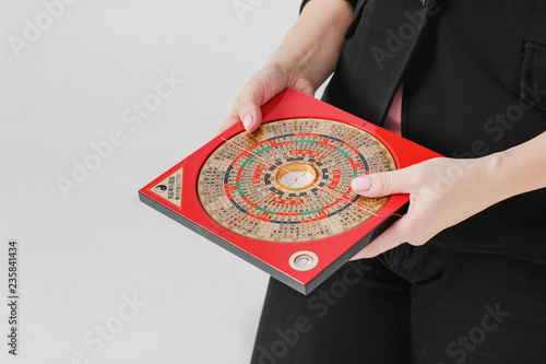 Fotografía  Chinese compass Lopan for Feng Shui technique in female hands isolated