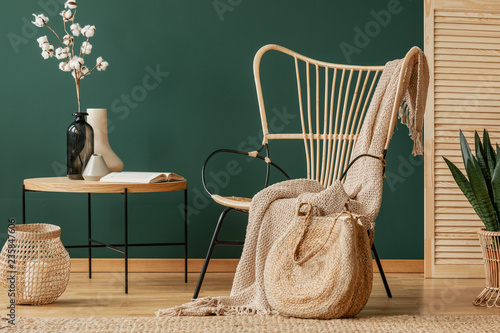 Photo  Blanket on rattan armchair next to table with flowers in green flat interior with lantern