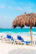 Beach sunbeds and umbrella on white beach