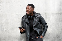 Young Black Man In Leather Jacket Smiling While Holding Cellphone