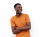smiling young african american man with arms crossed and t shirt against isolated white background