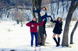 group of friends having fun in the park in winter near the river