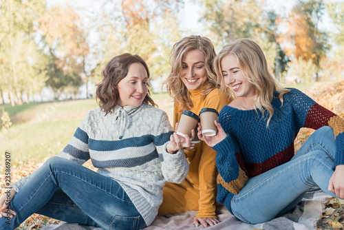 Fotografie, Obraz  Cheerful attractive three young women best friends having picnic and fun together outside