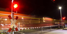 Closed Railroad Crossing With Passing Train At Night Panorama
