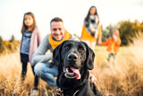 Fototapeta Zwierzęta - A young family with two small children and a dog on a meadow in autumn nature.