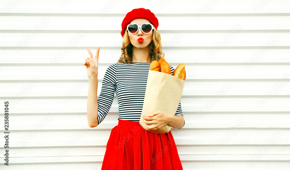 Fototapety, obrazy: Portrait pretty cool girl wearing french red beret holding paper bag with long white bread baguette on white wall background