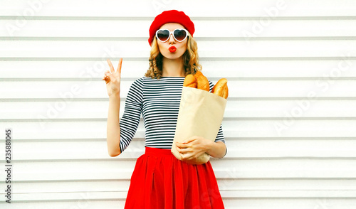 Obraz Portrait pretty cool girl wearing french red beret holding paper bag with long white bread baguette on white wall background - fototapety do salonu