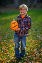 Portrait Of A Smiling Boy Standing In The Garden Holding A Jack-o-lantern, Untied States