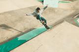 Guy practicing skateboarding and doing tricks in a skatepark