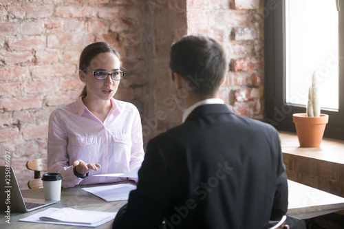 Photo Young woman advises client, explains terms of contract or discussing services
