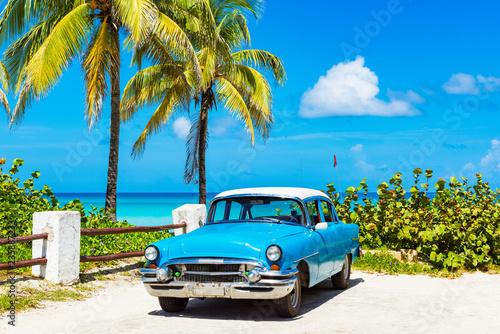 Foto auf Leinwand Bekannte Orte in Amerika Amerikanischer blauer Oldtimer parkt vor dem Strand in Varadero Cuba - Serie Cuba Reportage