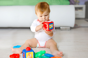 Fototapeta Adorable baby girl playing with educational toys in nursery. Happy healthy child having fun with colorful different toys at home. Kid trying to build plastic pyramid and using blocks with letters