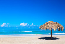 Straw Umbrella On Empty Seaside Beach In Varadero, Cuba. Relaxation, Vacation Idyllic Background.