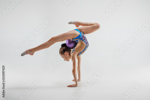 Spoed Foto op Canvas Gymnastiek The teen female little girl doing gymnastics exercises isolated on a gray studio background. The gymnastic, stretch, fitness, lifestyle, training, sport concept