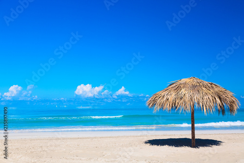 Straw umbrella on empty seaside beach in Varadero, Cuba. Relaxation, vacation idyllic background.