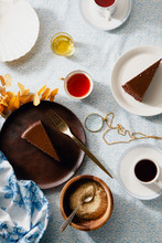 Overhead Image Of Tea Party With Chocolate Cheesecake Slices On Various Plates.
