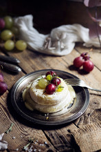 Cheese With Fresh Grapes On Rustic Table
