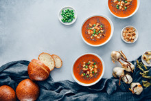 Overhead View Of Vegan Tomato Soup Served In Bowl With Bread Rolls
