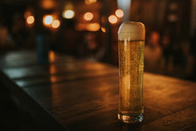 Blonde Beer Pint On A Wood Table, With Pub Lights In The Background At Night, And Left Copyspace